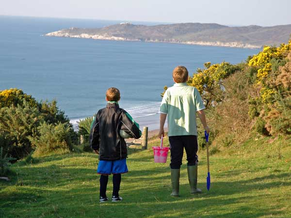 Boys walking down to Woolacombe beach while staying at Pickwell Barton Holiday cottages