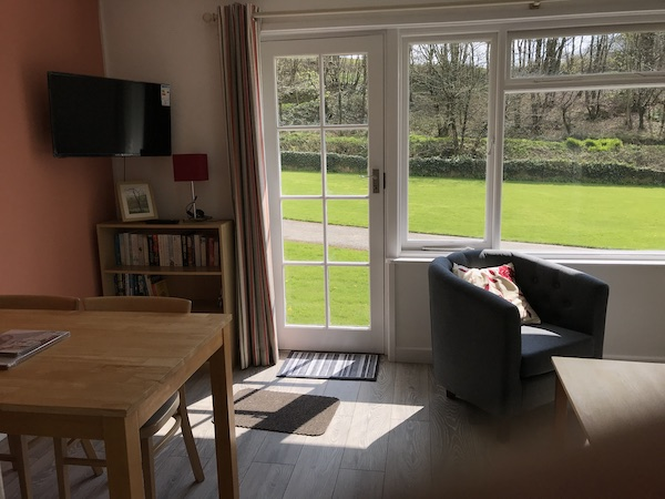 Grey laminate floor, wall mounted TV/DVD player and view of the lawn