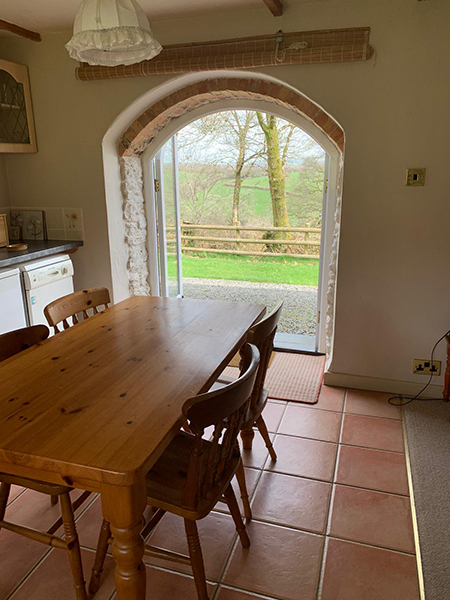Enjoy a family meal at the bright dining area at Hollacombe Farm Self-Catering.