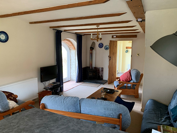 A cosy living room awaits guests at Hollacombe Farm Holiday Cottage.